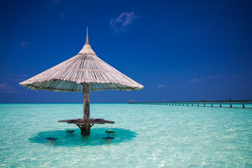 Bamboo beach umbrella with bar seats in the water