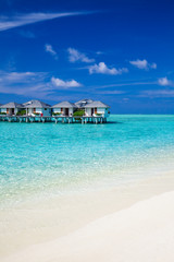 Water villas in the ocean and white sandy beach
