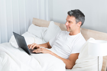 Man Relaxing On Bed Using Laptop