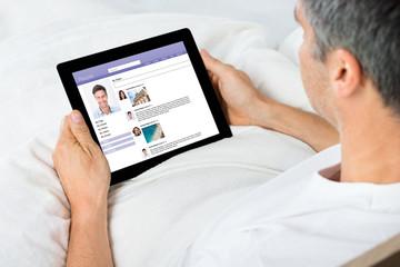 Man Chatting On Social Network Sites Using Digital Tablet