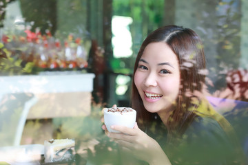 Young Asian women holding a cup of coffee with split tone beside