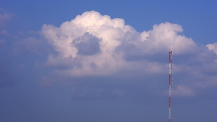 Time-lapse footage of cloud move behind telecommunication pole