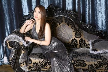 ソファーに座るイブニングドレスの女性