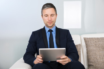 Businessman On Couch Looking At Digital Tablet