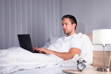 Man In Bedroom Using Laptop