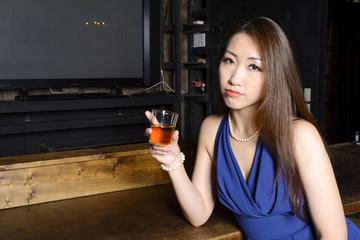 カウンターでグラスを持つカクテルドレスの女性