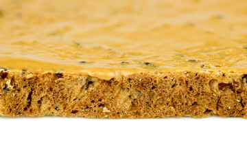 Macro closeup of edge of peanut butter toast