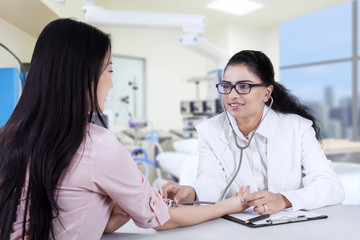 Asian doctor listening the patient heartbeat