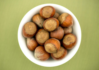 Bowl of hazelnuts against textured green background