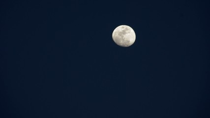 Time-lapse footage of the rising moon with the sky become dark
