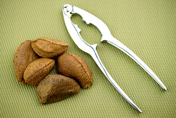 Brazil nuts with nut cracker on textured background