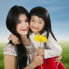 Child holding flower with her parent