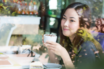 Young Asian women holding a cup of coffee beside mirror