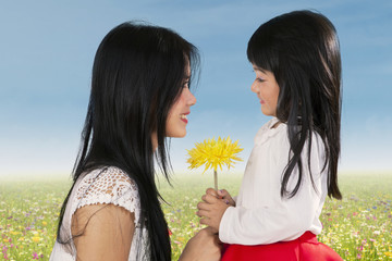 Cute girl giving flower to her mom