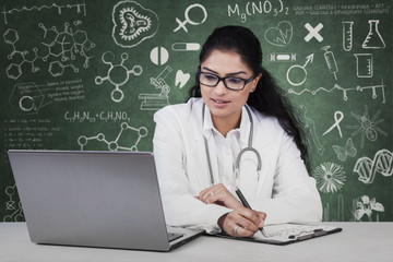 Doctor working with laptop and clipboard
