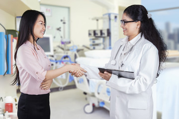 Friendly doctor shaking hands with patient in the clinic