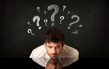 Sitting businessman under question marks