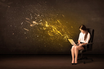 Businesswoman with laptop and energy explosion on background