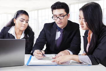 Male manager reading a document with partners