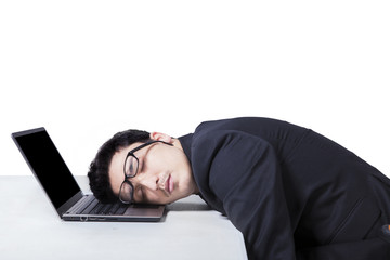 Male manager sleeping on laptop