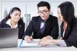 Multi ethnic businessteam signing a document