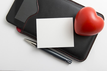 Closeup of tablet and red heart on white background