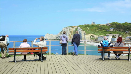 Group of tourists enjoy the view of famous cliffs of Etretat