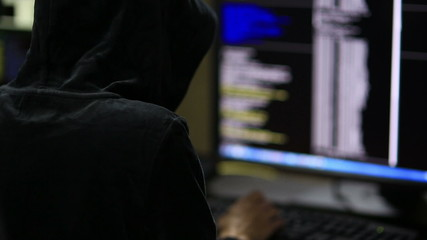 Hacker in hood cracking code using laptop and computers from his