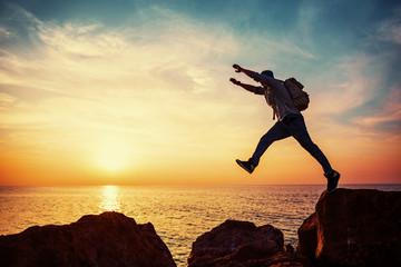 brave man jumping over rocks at sunset
