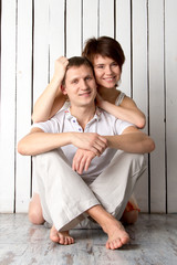 Young couple is hugging near the white wooden wall