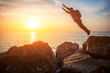 brave man with backpack jumping over rocks at sunset