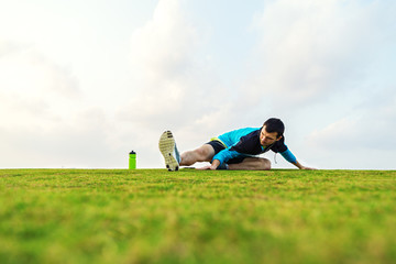 sportsman doing warming stretching exercise in the park