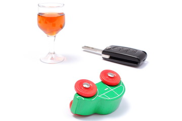 Overturned model vehicle, glass of wine and car key