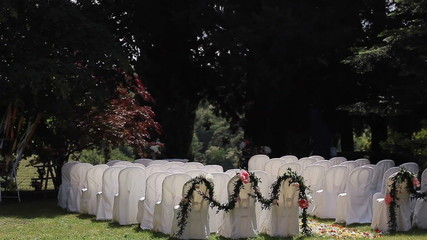 Rows of chairs on lawn ready for outdoor wedding ceremony