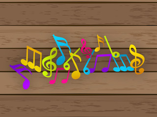 Colorful musical notes on wooden background.