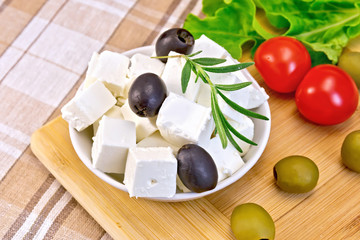 Feta with olives in bowl on fabric and board