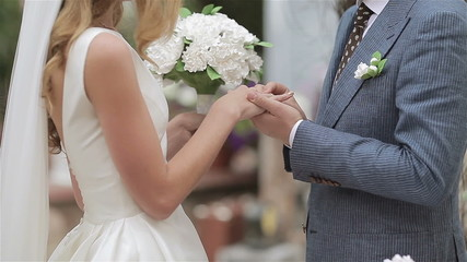 Groom puts a wedding ring on finger of a bride