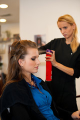 Young woman in hairdresser saloon having a treatment and haircut