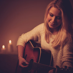 Young blonde woman playing guitar in candle light