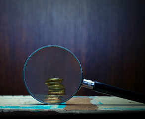 Magnifier and gold coins.
