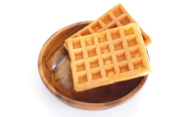 Delicious sweet waffle in wooden bowl on white background