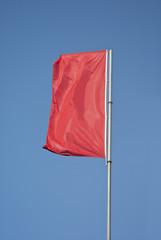 Red flag flying on blue sky