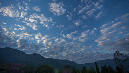 Time lapse of clouds move over mountain at sunset