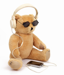 Teddy Bear listening music. Isolated on white