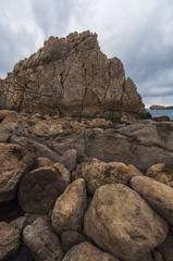 Rocky beach in a stormy day with dark cloudy sky