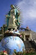 Statue of virgen of Guadalupe over the world