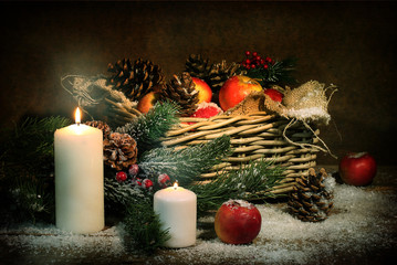 Apples and cones in a basket, candles and fur-tree branches in s