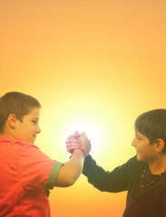 Two teenage boys shaking hand against sunny sky