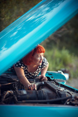 Retro girl repairing blue Cadillac
