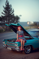 Retro girl sitting on blue Cadillac with opened hood